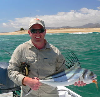 Jamie Clark showinf off his first rooster fish on a fly